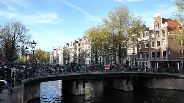 vídeos y material grabado en eventos de stock de calles de amsterdam, famosos puentes, bicicletas y arquitectura después de las restricciones y cierres covid - estrecho