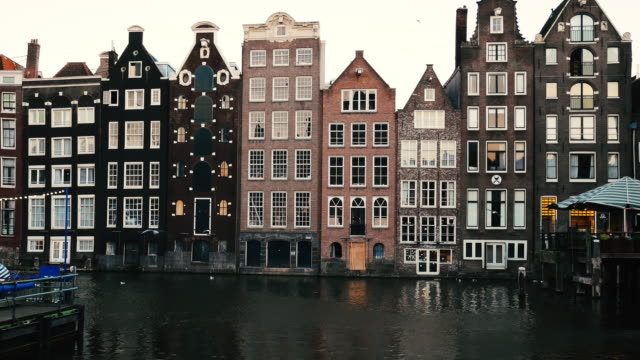 streets of amsterdam, famous bridges, bicycles and architecture in iconic european city in netherlands - canal stock videos & royalty-free footage