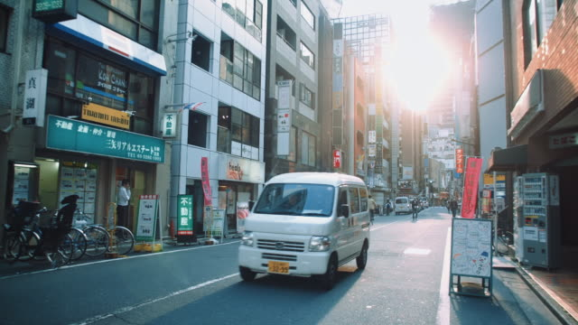 ws, streets of shinjuku dristrict, sun shining through the skyline, people walking by - retail place stock videos & royalty-free footage