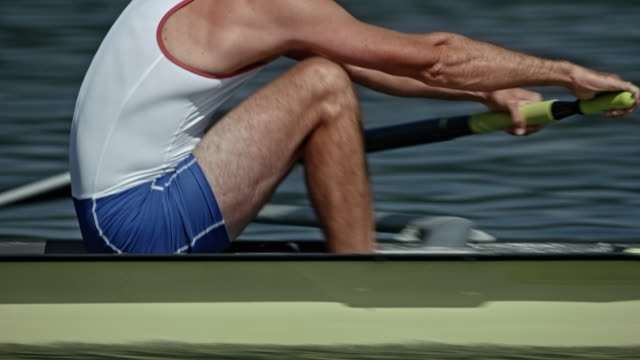 ts strength of a male rowing athlete gliding across a lake in coxless pair - rowing stock videos & royalty-free footage