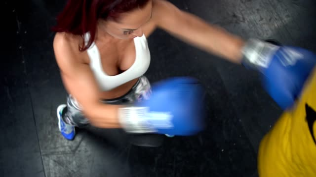 stress relief - overhead top shoot of a woman punching the bag in gym - punch bag stock videos & royalty-free footage