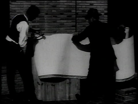 1921 montage stress testing asbestos sheet / united states - 1921 stock-videos und b-roll-filmmaterial