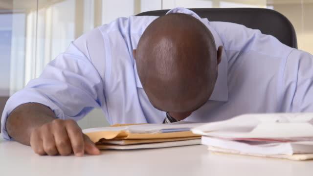 Stressed African-American Businessman banging head on desk