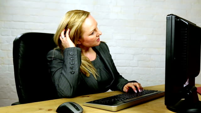 stressed attractive powerful blonde female boss typing at computer