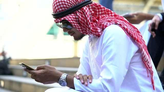 Stressed bearded Arab businessman playing mobile phone sitting on the walkway outdoor.