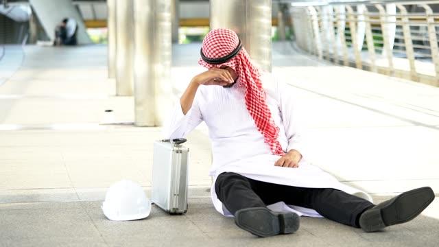 stressed bearded arab businessman sitting on the walkway outdoor. - displeased stock videos & royalty-free footage