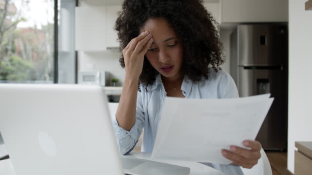 stressed black woman working from home looking at a document very upset - financial bill stock videos & royalty-free footage