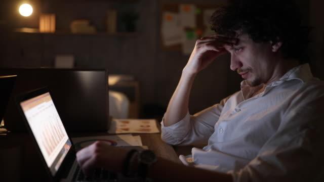 vídeos de stock, filmes e b-roll de empresário estressado sentindo dor de cabeça enquanto fazia hora extra à noite - com as mãos na cabeça