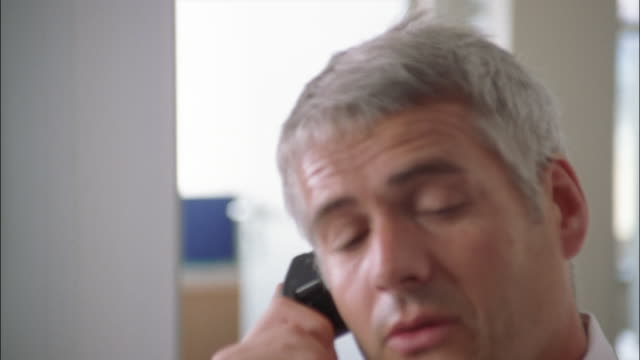 a stressed businessman hangs up the telephone and rubs his eyes and head. - irritation stock videos & royalty-free footage