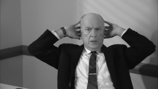 vidéos et rushes de b/w ms stressed businessman leaning back with head in hands/ man rubbing temples and pounding on head with fists as if he has headache/ new york city - hitting