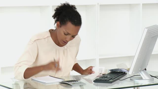 vidéos et rushes de ms stressed businesswoman doing paperwork at desk / cape town, western cape, south africa - une seule femme d'âge moyen