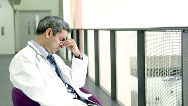 Stressed doctor sitting in chair