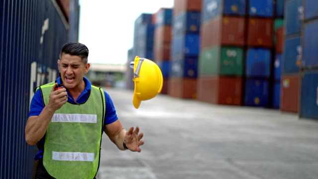 4k stressed male engineer shouting at walkie-talkie in front of cargo container stacks in shipping port - distraught stock videos & royalty-free footage