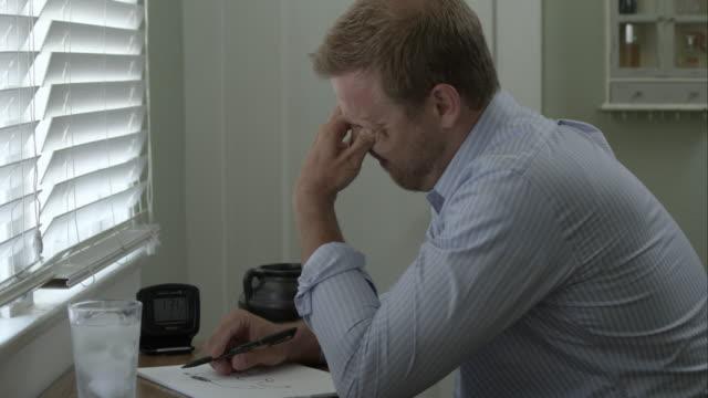 Stressed man at desk taking some pills.