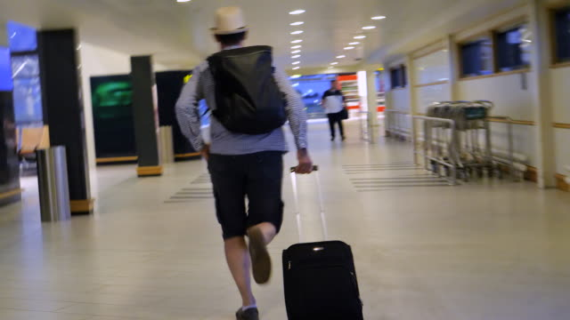 stressed man running with suitcase and backpack at airport to reach his gate - emotional stress stock videos & royalty-free footage