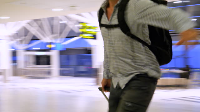 gestresster mann läuft mit koffer und rucksack am flughafen, um sein tor zu erreichen - passagier stock-videos und b-roll-filmmaterial