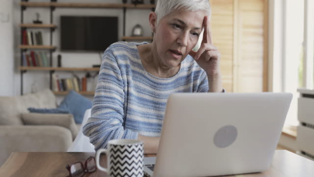 stressed mature woman using computer at home. - terza età video stock e b–roll