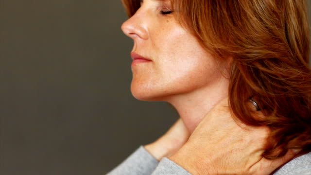 stressed mature woman with neck pain - profile stock videos & royalty-free footage