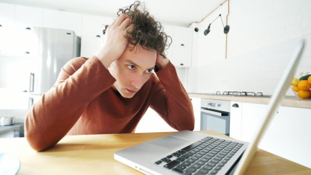 Stressed men working at home on laptop.