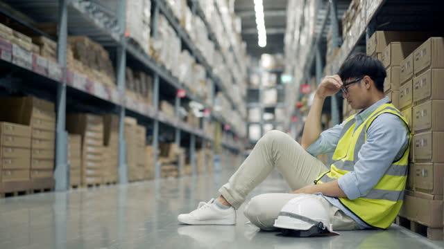 vídeos de stock e filmes b-roll de stressed warehouse worker sitting in front of shelf at warehouse - trabalhador de armazém