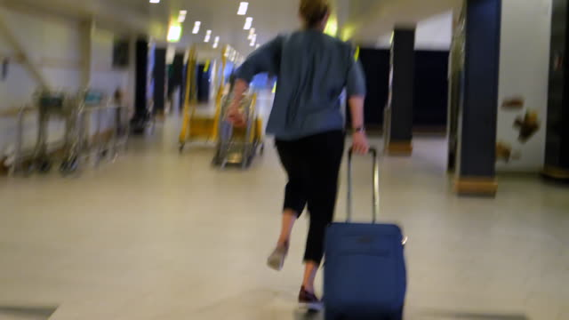 stressed woman running with suitcase at airport to reach her gate - telecamera traballante video stock e b–roll