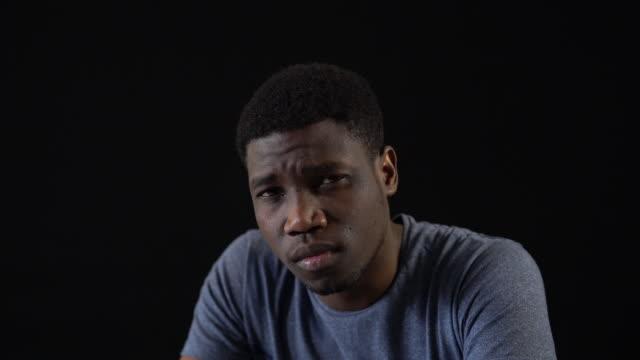 betonte jungen mann vor schwarzem hintergrund - t shirt stock-videos und b-roll-filmmaterial