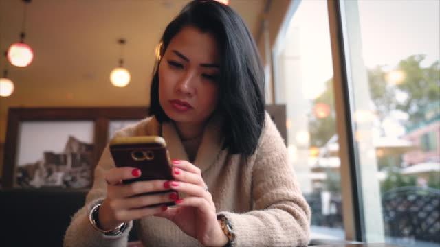 stressande asiatiskapojke kvinna sändande text meddelande vid rörlig telefonerna - relationsproblem bildbanksvideor och videomaterial från bakom kulisserna