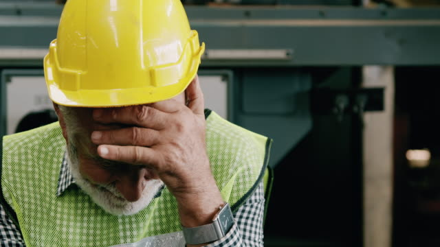 stressful senior industrial worker portrait, hands cover head. slowmotion, caucasian male, overalls, helmets. industrial and manufactory concept. - non us location stock videos & royalty-free footage
