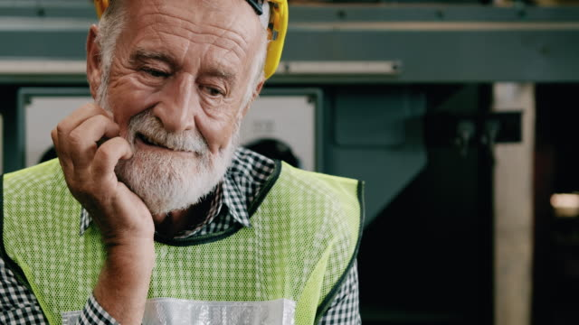 stressful senior industrial worker portrait, straching face. slowmotion, caucasian male, overalls, helmets. industrial and manufactory concept. - non us location stock videos & royalty-free footage