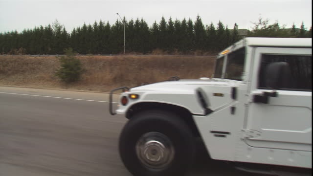 stockvideo's en b-roll-footage met a stretch humvee travels on a highway. - humvee