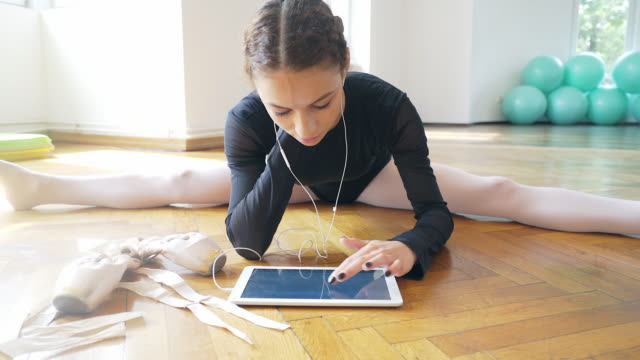 stretching and using a digital tablet. - dance studio stock videos and b-roll footage