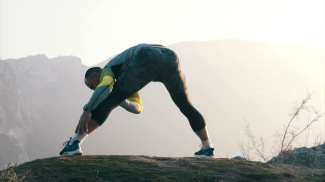stretching exercises on top of the mountain - pursuit sports competition format stock videos & royalty-free footage