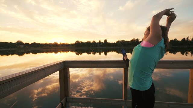 vídeos de stock, filmes e b-roll de exercícios de alongamento. - só uma mulher de idade mediana