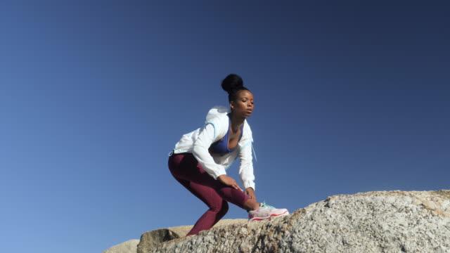 vídeos de stock, filmes e b-roll de stretching sportswoman on rocks, low angle - sutiã para esportes