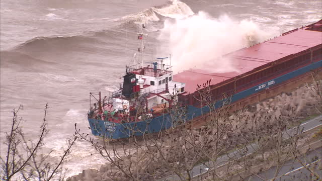 a stricken cargo ship which ran aground in rough seas last night has leaked oil into surrounding waters salvage counter pollution experts are working... - ship stock videos & royalty-free footage