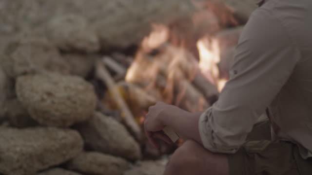 vídeos de stock, filmes e b-roll de striking a match at fireplace by the shore. - firewood