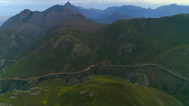 a striking aerial over distant cars moving slowly along a road winding through a lush hillside - cape town, south africa - テーブルマウンテン国立公園点の映像素材/bロール