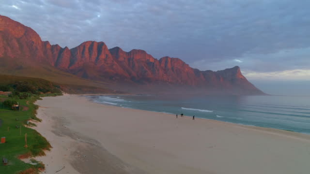 a striking aerial over people strolling on a large beach with distant red mountains at dusk - cape town, south africa - remote location stock videos & royalty-free footage