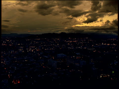 Striking amber sunset pan left over Bogota city at night houses and city buildings illuminated