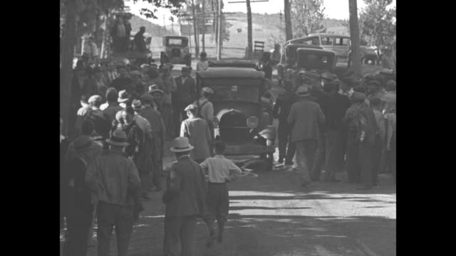 striking farmers run toward an approaching truck / men milling around near a couple of cars / farmers pour milk out of metal canisters as they stand... - great depression stock videos & royalty-free footage
