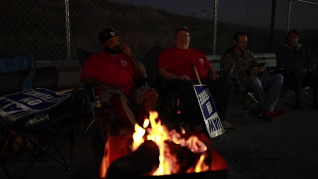 striking gm workers sit near a campfire staying war while holding picket signs. 10182019 - bedford, indiana, usa: united auto workers local 440... - war stock-videos und b-roll-filmmaterial