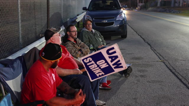 striking gm workers sit near a campfire staying war while holding picket signs united auto workers local 440 members continue to picket outside the... - labor union stock videos & royalty-free footage