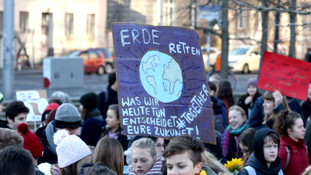 striking high school students march with banners on climate protection at the starting point to protest for more effective government climate change... - environmental issues stock-videos und b-roll-filmmaterial