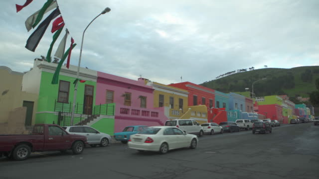 a striking lockdown of cars driving and parked on street in front of long row of colorful houses - cape town, south africa - cars parked in a row stock videos & royalty-free footage