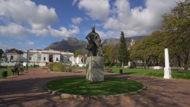 stockvideo's en b-roll-footage met a striking pan of a bronze statue in the rhodes memorial park under tall dark cliffs on a sunny day - cape town, south africa - memorial