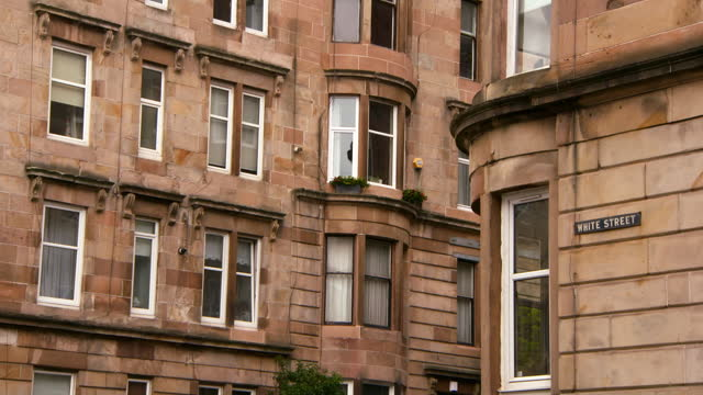 striking sandstone georgian tenement building with large windows on overcast day - glasgow, scotland - ジョージア調点の映像素材/bロール