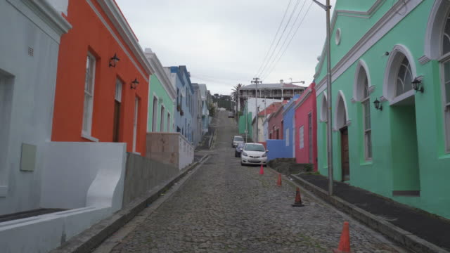 stockvideo's en b-roll-footage met a striking pov walking down a cobblestone street lined with small cars and picturesque brightly painted houses - cape town, south africa - famous place