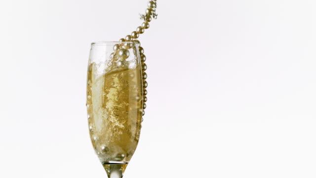 stockvideo's en b-roll-footage met string of pearls falling into champagne glass - parel juwelen
