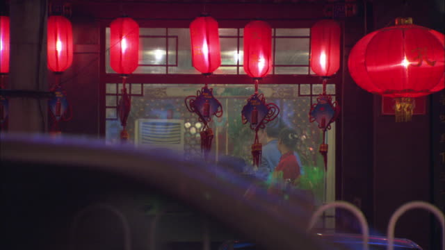 WS String of red lanterns hanging over exterior of restaurant, customers inside / Beijing, China