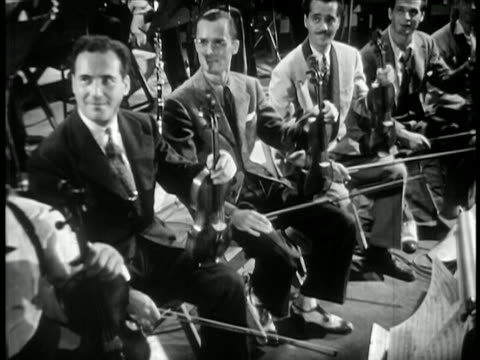 b/w 1940 string section of band sitting + tapping feet to music / feature film - swing video stock e b–roll